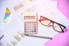 Business graph chart report paper financial document with calculator pen and glasses royalty free stock photo