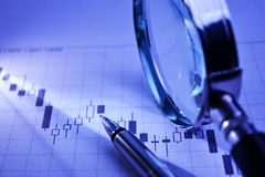 Business graph with pen and magnifying glass Royalty Free Stock Photo
