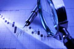 Business graph with pen and magnifying glass stock photography