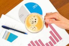 Business graphics and cup of coffee Royalty Free Stock Photo