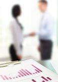 Business graphs. Close up of business graphs with blurred figures of office workers in the background Royalty Free Stock Image