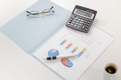 Business graphs with a calculator, a pen and glasses Stock Photo