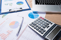 Business graphs and charts on a wooden desk with a calculator, c Royalty Free Stock Photo