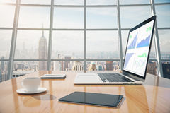 Business graphs on laptop screen, coffee mug, digital tablet on. The table in sunny office with windows in floor Stock Images
