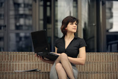 Business is great. Young attractive  business woman outdoors with a laptop in her lap looking far away Stock Images