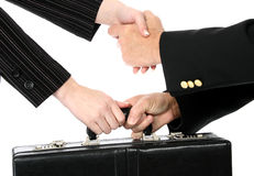 Business Greeting. Man and woman shaking hands and passing briefcase over white royalty free stock image