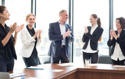 Business group clapping and smiling. Business people group clapping and smiling in office standing around meeting table Royalty Free Stock Photos