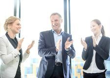 Business group clapping and smiling. Business people group clapping and smiling in office standing around meeting table Stock Photo