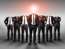 Business group without heads and one businessman in the center with light bulb Royalty Free Stock Photography