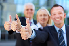 Business group holding thumbs up stock images