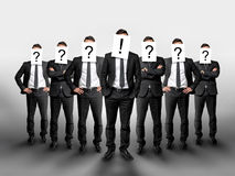 Business group with question marks on their heads and one businessman in the center has exclamation mark Stock Photos