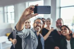 Business group selfie. Business people taking selfie of in the office. Business team taking selfie together at startup, with focus on mobile phone stock photo