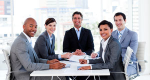 Business group showing ethnic diversity. In a meeting smiling at the camera Royalty Free Stock Images