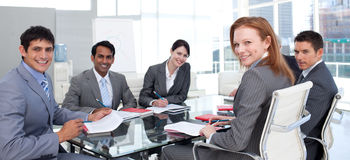 Business group showing ethnic diversity smiling. In a meeting Stock Photo