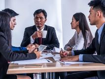 Business groups propose management plans to executive directors through tablets.  royalty free stock images
