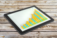 Business growing up graph on digital tablet screen on wooden tab Royalty Free Stock Images