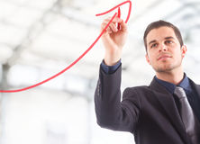 Business growth. Businessman drawing a rising arrow, representing business growth royalty free stock image