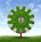 Business Growth. Growing business concept with a tree and branches with leaves in the shape of a machine gear or cog as an industrial symbol of financial success Royalty Free Stock Image