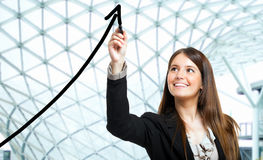 Business growth. Beautiful woman tracing a rising arrow, representing business growth Stock Image