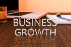 Business Growth. Letters on wooden desk with laptop computer and a notebook. 3d render illustration Royalty Free Stock Photography