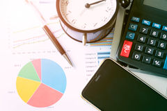 Business growth chart analysis report with pen, calculator, mobi. Le phone and alarm clock on table in office. Accounting, business concept. Soft light and Royalty Free Stock Photo