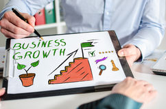 Business growth concept on a clipboard. Businessman showing business growth concept on a clipboard Stock Photography