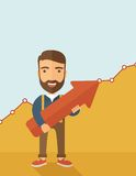 Business growth. A lucky young  hipster Caucasian man with beard cheerfully carrying a red arrow pointing upward showing for his successful plan in business Stock Photo