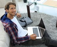 Business guy with laptop sitting on carpet in living room. Business guy with laptop sitting near sofa on carpet in living room Stock Images