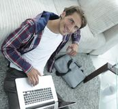 Business guy with laptop sitting on carpet in living room. Business guy with laptop sitting near sofa on carpet in living room Royalty Free Stock Photo