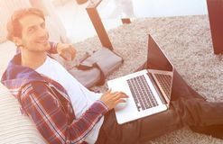 Business guy with laptop sitting on carpet in living room. Business guy with laptop sitting near sofa on carpet in living room Royalty Free Stock Images