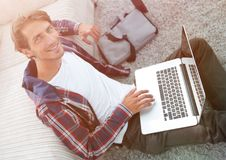 Business guy with laptop sitting on carpet in living room. Business guy with laptop sitting near sofa on carpet in living room Royalty Free Stock Photos