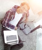 Business guy with laptop sitting on carpet in living room. Business guy with laptop sitting near sofa on carpet in living room Stock Photos