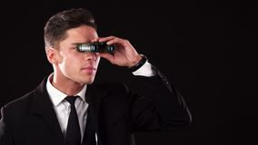 A business guy is trying to see something in the distance through binoculars. The guy is trying to consider something in the distance. He`s screwing up his eyes stock photography