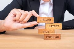 Business hand building trends concept with wooden blocks on wood. Popular, Hot, Latest, Trends royalty free stock image