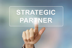Business hand clicking strategic partner button. Business hand pushing strategic partner button on blurred background Stock Photography