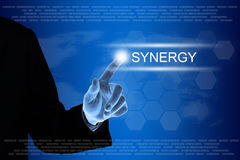 Business hand clicking synergy button on touch screen. Business hand pushing synergy button on a touch screen interface Royalty Free Stock Photo