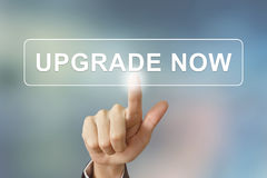 Business hand clicking upgrade now button on blurred background Royalty Free Stock Photos