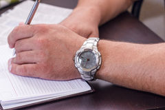 Business hand with the clock, holding pen and notebook Stock Images