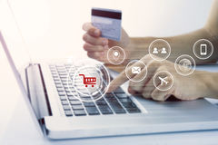 Business hand holding credit card with computer and shopping. Online payment e-commerce internet technology concept Royalty Free Stock Photos