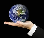 Business hand holding earth over black Royalty Free Stock Images