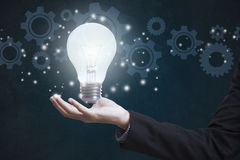 Business hand holding electric light bulb with gear wheels. royalty free stock image