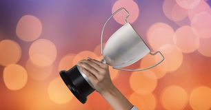 Business hand holding trophy against abstract background Royalty Free Stock Photo