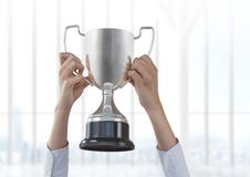 Business hand holding trophy against window Stock Photos