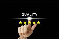 Business hand pushing quality on screen Stock Photo