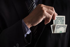 Business hand is putting money in the pocket Stock Photo