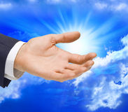 Business Hand Reaching Out. A hand reaching out to help with sky in the background Stock Photos
