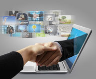 Business  hand reaching out from screen laptop shake Hand Stock Photos