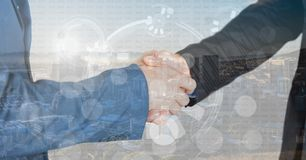 Business hand shake overlap with city, graphs and numbers. Digital composite of business hand shake overlap with city, graphs and numbers Stock Image