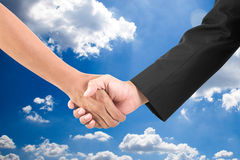 Business hand shake on a summer clouds background royalty free stock images