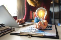Light bulb with business hand working with laptop computer a stock photos